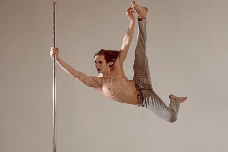 El atleta de sexo masculino de la danza de poste, aesha partió en fondo gris foto de archivo