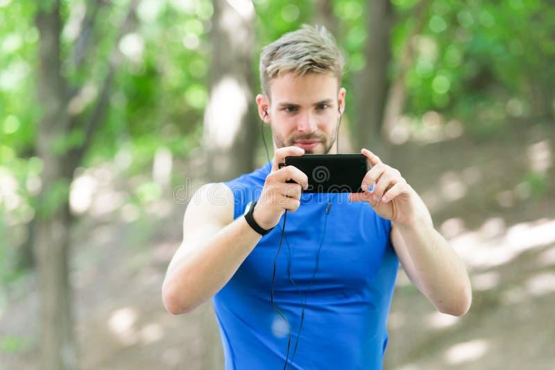El atleta del hombre concentró el fondo de la naturaleza de la foto del smartphone de la toma de la cara Podómetro y auriculares  imágenes de archivo libres de regalías
