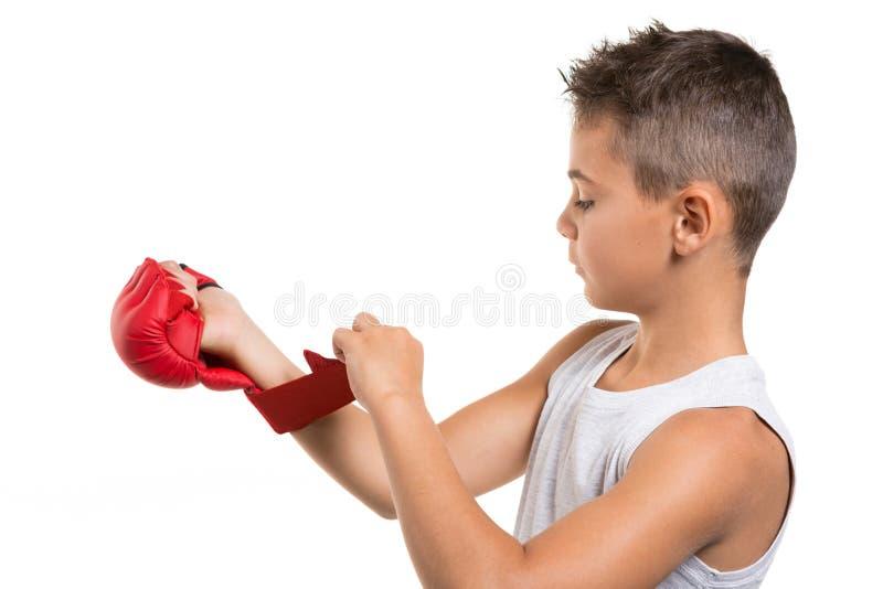 El atleta del muchacho pone un guante rojo para el karate, en un fondo blanco fotografía de archivo