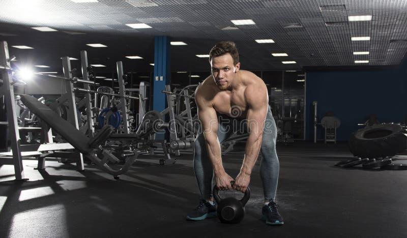 El atleta descamisado muscular que hace el kettlebell balancea en ajuste moderno imagenes de archivo