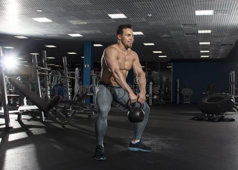El atleta descamisado muscular que hace el kettlebell balancea en ajuste moderno fotos de archivo
