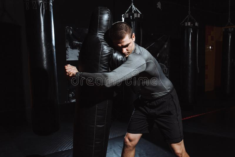 El atleta hace el tiro del maniquí, el entrenamiento del luchador, el gimnasio para luchar foto de archivo libre de regalías