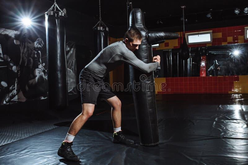 El atleta hace el tiro del maniquí, el entrenamiento del luchador, el gimnasio para luchar fotografía de archivo