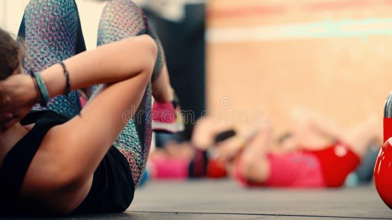 El atleta hermoso de la muchacha enganchó a ejercicios en el trabajo abdominal fotos de archivo