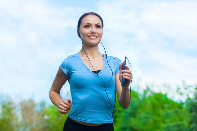 El atleta joven que corre en el parque y escucha la música en el verano, ejercicio de la mañana imagenes de archivo