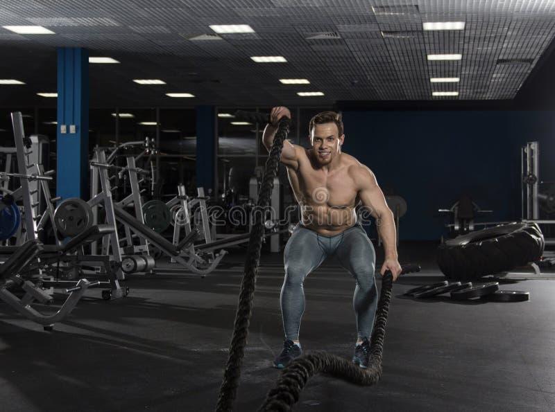 El atleta muscular con batalla ropes ejercicio en ce moderno de la aptitud fotos de archivo