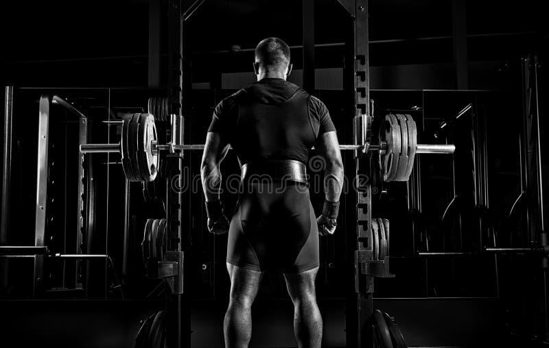 El atleta profesional se coloca delante de las barras con un barbell fotos de archivo libres de regalías