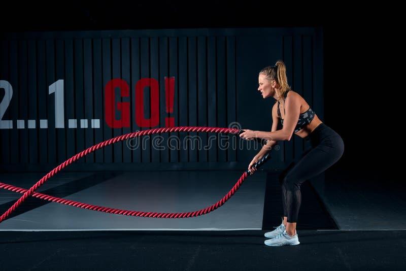 El atleta que se resuelve con batalla ropes en el gimnasio cruzado foto de archivo libre de regalías