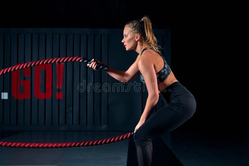El atleta que se resuelve con batalla ropes en el gimnasio cruzado imagen de archivo