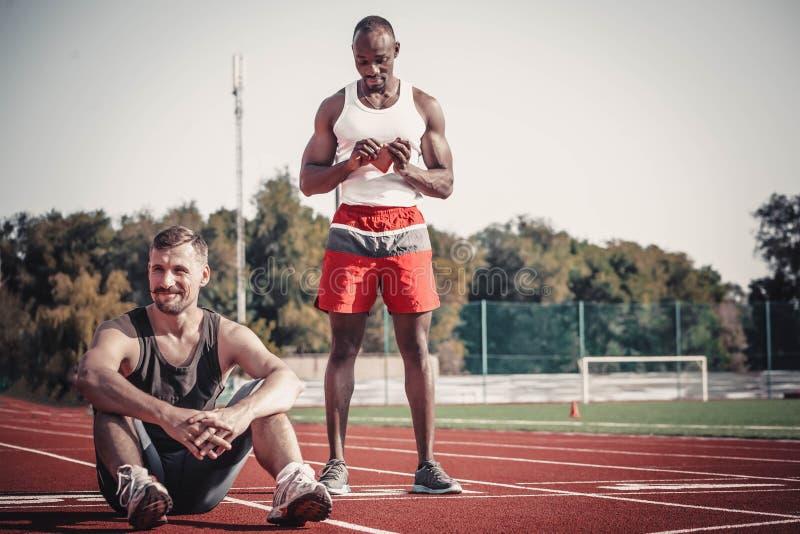 El atleta se sienta y sonríe mientras que su socio negro rasga el paquete fotografía de archivo
