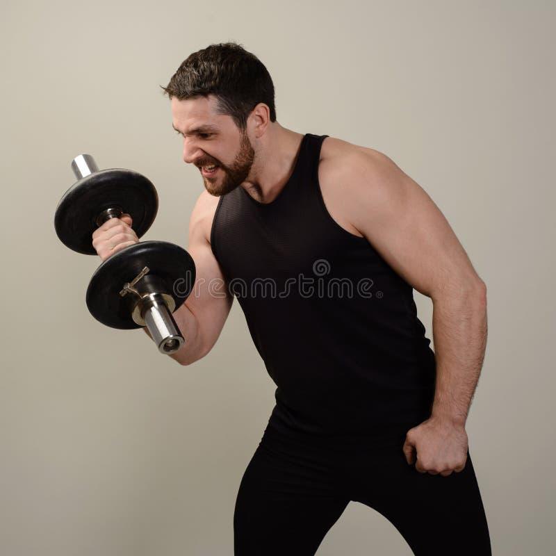 El atleta serio joven realiza un ejercicio con pesas de gimnasia para desarrollar el bíceps fotos de archivo libres de regalías