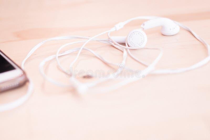 El auricular blanco con el alambre al teléfono móvil está en la tabla de madera ligera imagen de archivo