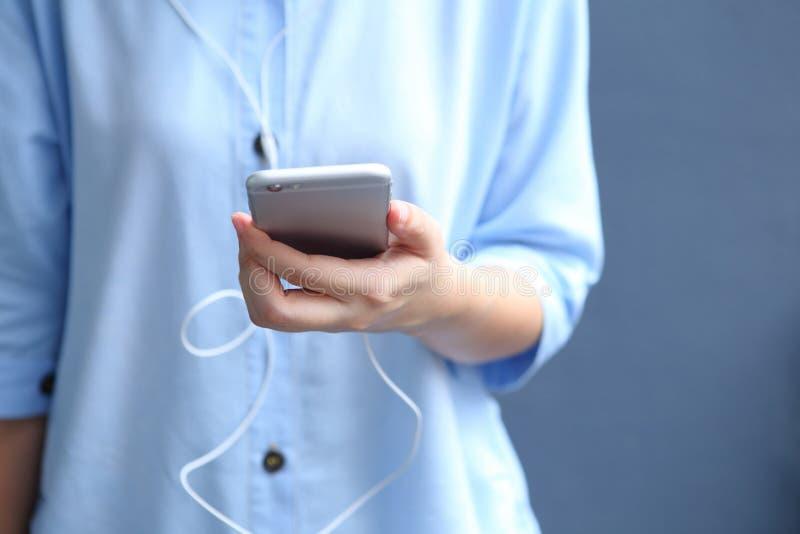 El auricular del desgaste de mujer con usar el smartphone para escucha canción fotografía de archivo