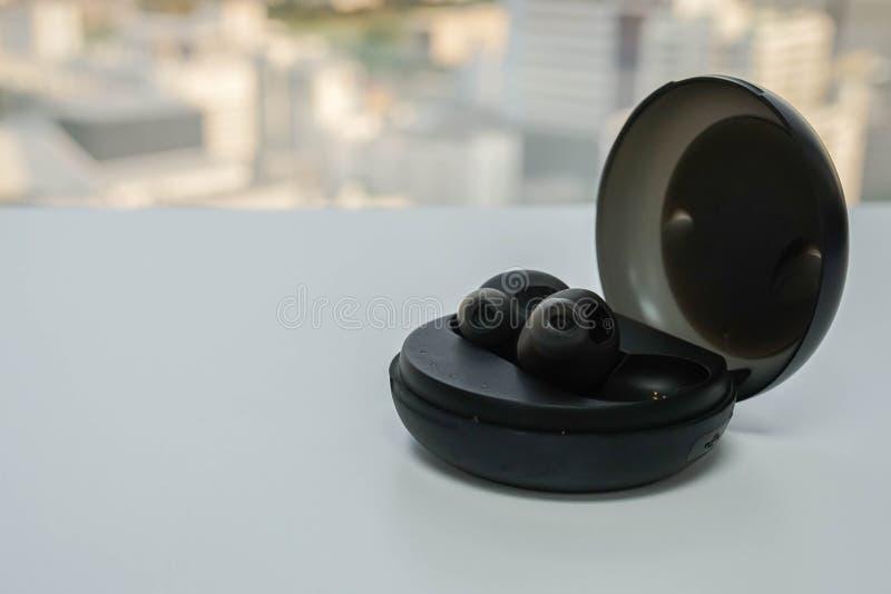 El auricular inalámbrico portátil con la caja de moda negra redonda para la música escucha fotos de archivo libres de regalías