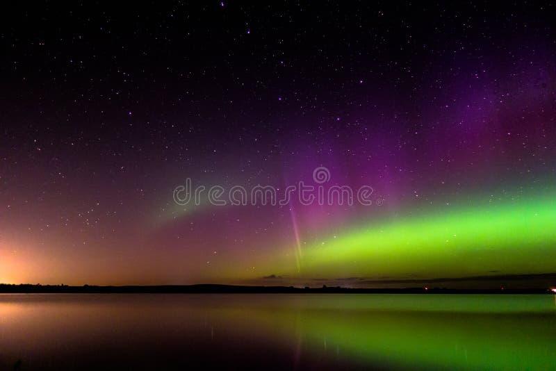 El aurora borealis con el arco del protón reflejó sobre un lago fotos de archivo
