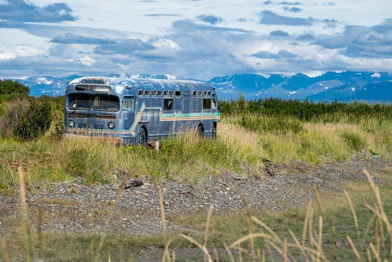 El autobús abandonado retro viejo se sienta adelante en un pantano a lo largo de Homer Spit en Alaska foto de archivo libre de regalías
