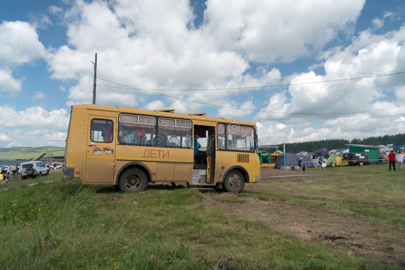 El autobús amarillo con la inscripción en el lado - niños - trajo niños al festival de música y soportes contra las tiendas foto de archivo libre de regalías