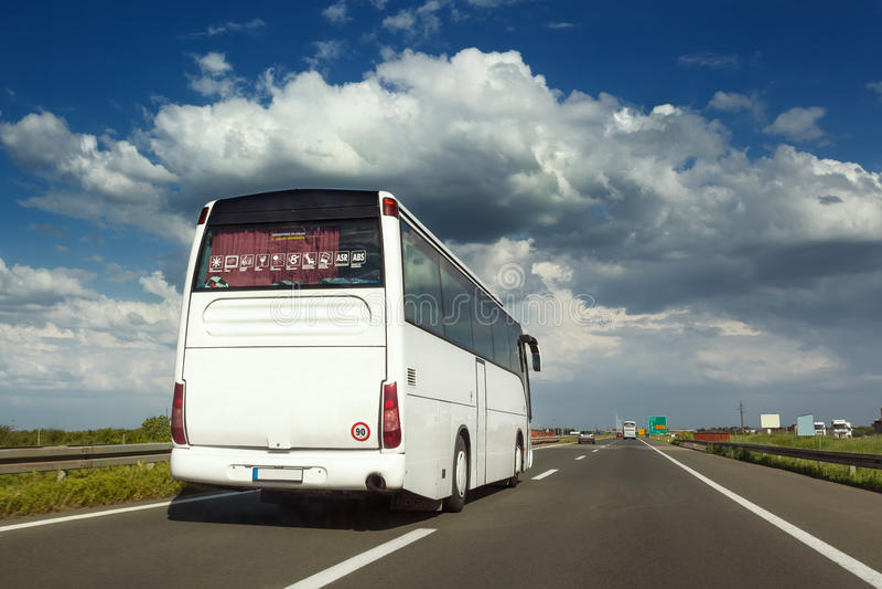 El autobús blanco es el alcanzar hecho en la carretera imágenes de archivo libres de regalías