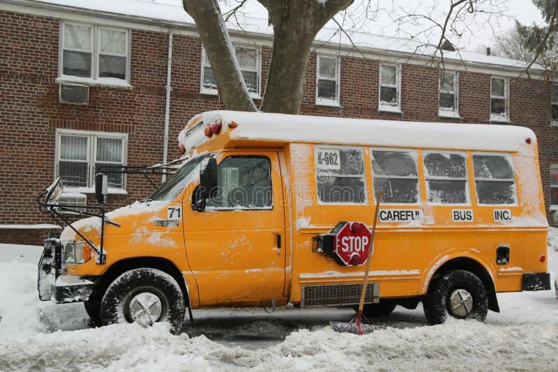 El autobús escolar debajo de la nieve en Brooklyn, NY después de la tormenta masiva Niko del invierno pega al noreste fotos de archivo