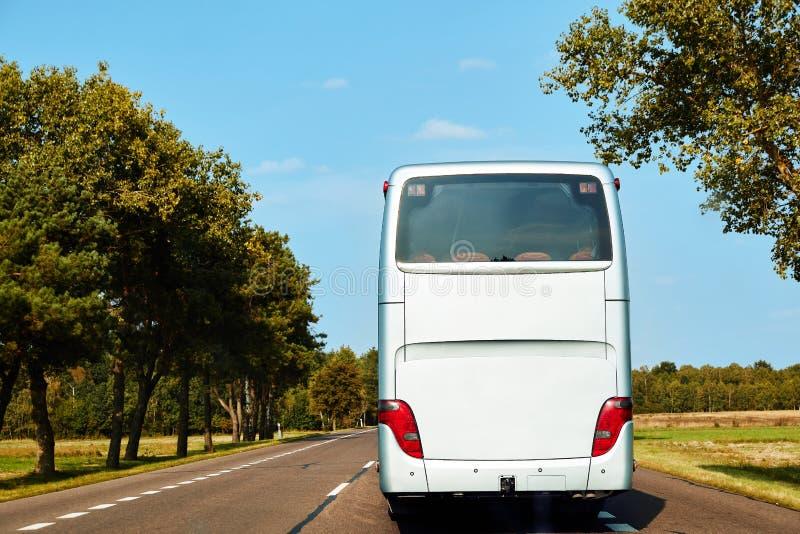 El autobús interurbano blanco está conduciendo a lo largo del camino imagenes de archivo