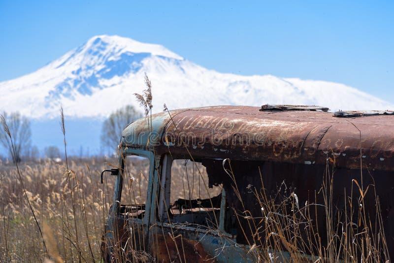 El autobús ruso soviético viejo abandonado y oxidado en el medio de las cañas y de la agricultura coloca con el Mt Ararat en el f imagen de archivo