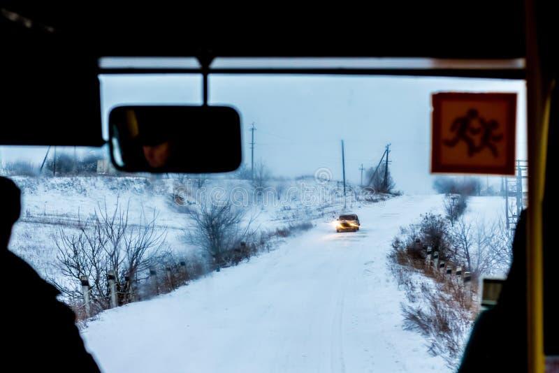 El autobús se mueve a lo largo del camino nevoso Condiciones meteorológicas complicadas en winter_ fotografía de archivo