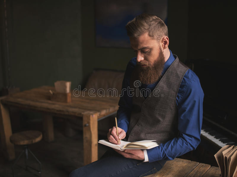 El autor barbudo alegre está escribiendo un poema imagen de archivo libre de regalías