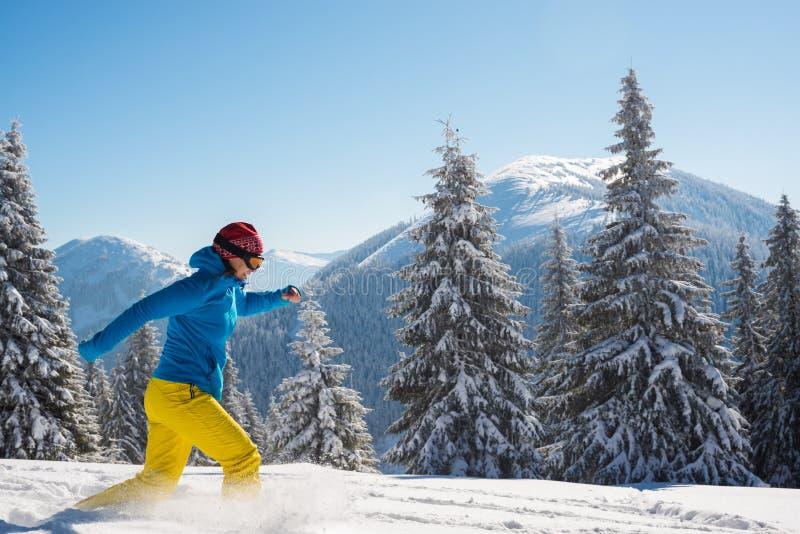 El aventurero alegre, mujer está corriendo en las montañas del invierno imágenes de archivo libres de regalías
