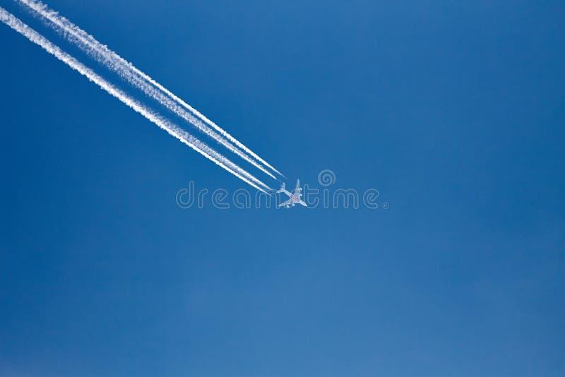 El avión con el vapor se arrastra en un cielo azul fotografía de archivo