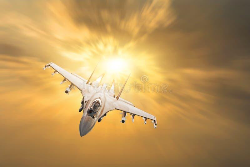 El avión de combate militar furioso con el fuego de los motores vuela en el cielo anaranjado de la puesta del sol fotografía de archivo