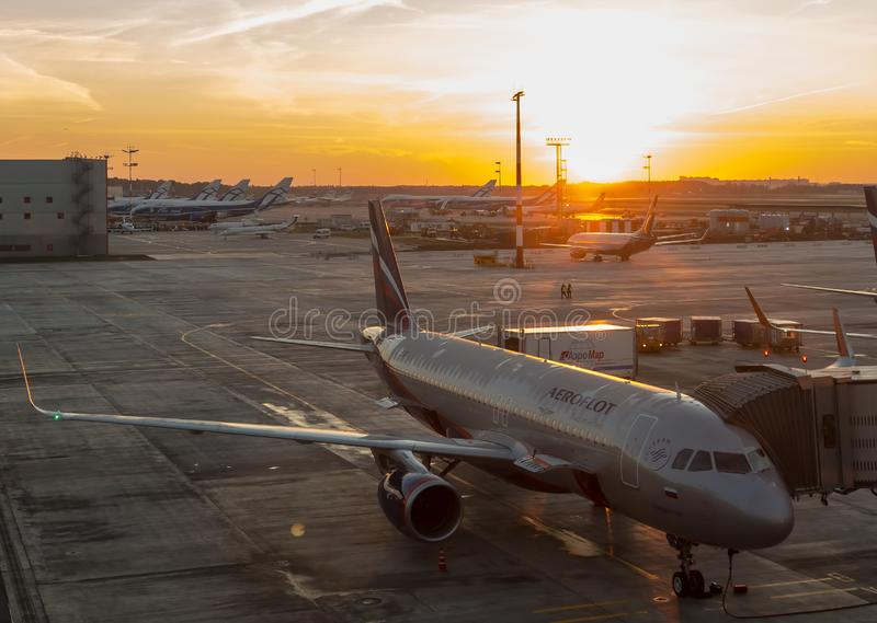 El avión de la línea aérea rusa Aeroflot preparado completamente para el embarque de pasajeros en el fondo del sol naciente fotos de archivo