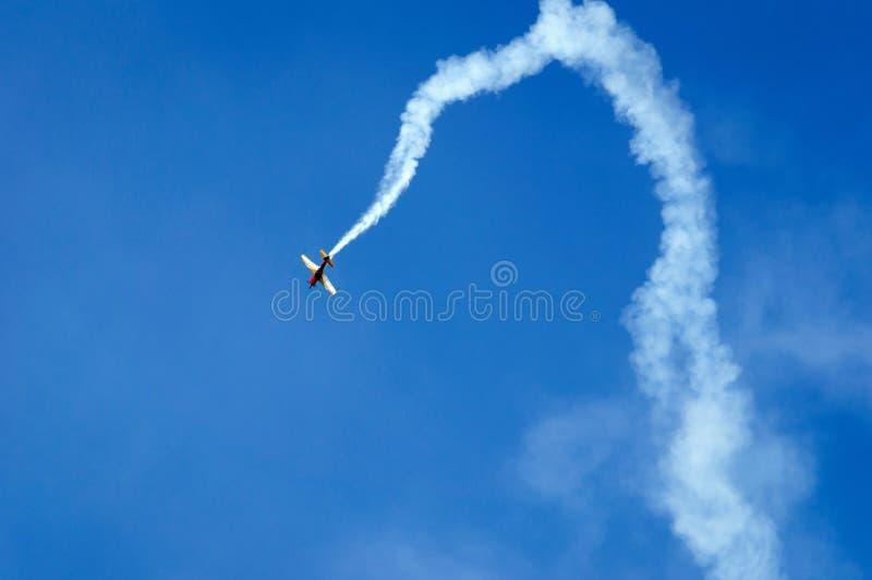 El avión de los deportes realiza figuras aeroacrobacias en el cielo en el salón aeronáutico foto de archivo libre de regalías