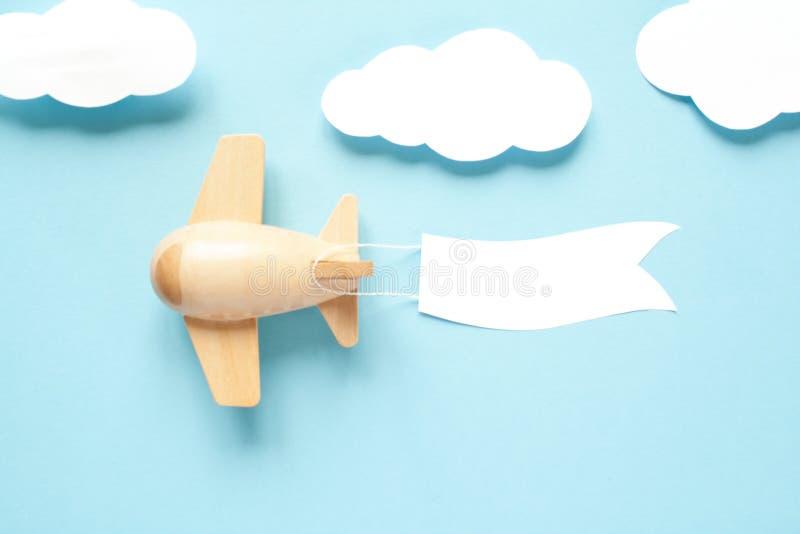 El avión de madera de los niños en el cielo lleva una bandera vacía foto de archivo