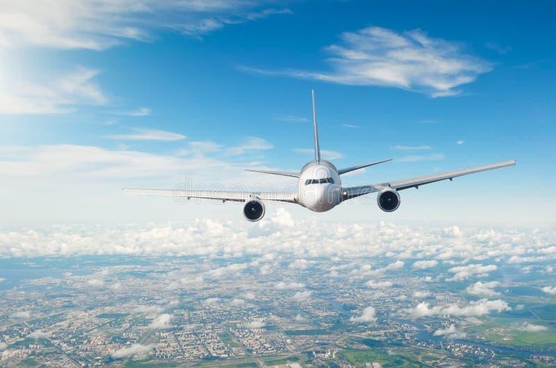El avión de pasajeros del pasajero vuela sobre la ciudad, una disminución en llegada del aeropuerto imagenes de archivo