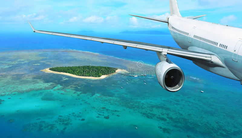 El avión de pasajeros vuela sobre la isla tropical imagenes de archivo