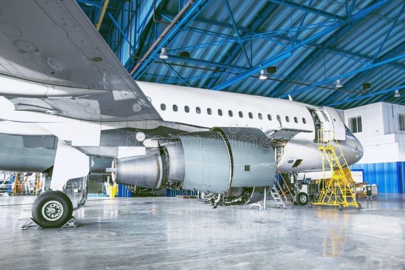 El avión está en el hangar de la aviación Reparación del tema y mantenimiento de las líneas aéreas del aeroplano imagenes de archivo