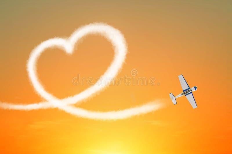 El avión ligero en el cielo dibuja el corazón blanco del amor del humo fotografía de archivo libre de regalías