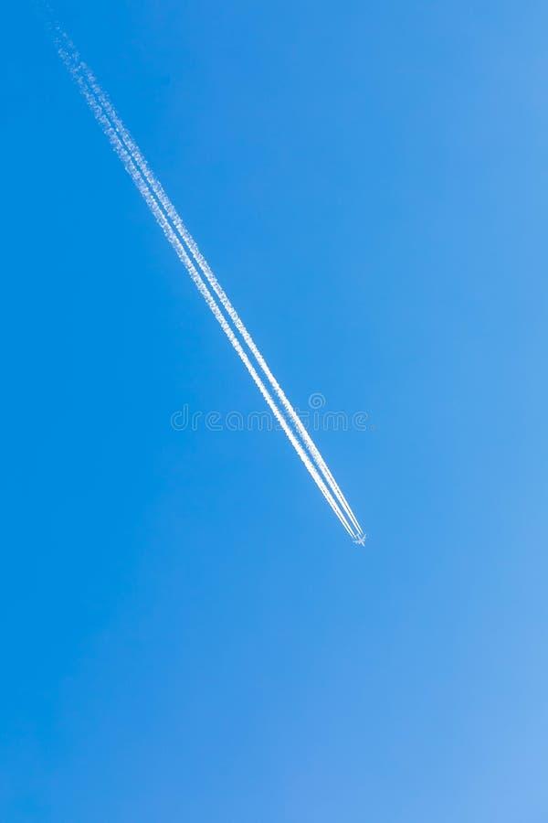 El avión vuela altamente en el cielo azul, fotografía de archivo libre de regalías