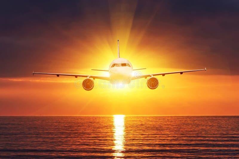 El avión vuela delante del sol Puesta del sol sobre el mar, vista del horizonte Superficie del agua con las ondas fotografía de archivo