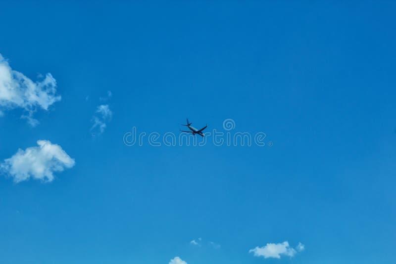 El avión vuela en el cielo con las nubes fotos de archivo