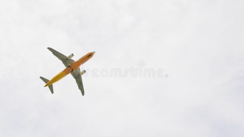 El avión vuela en el cielo en tiempo nublado fotos de archivo