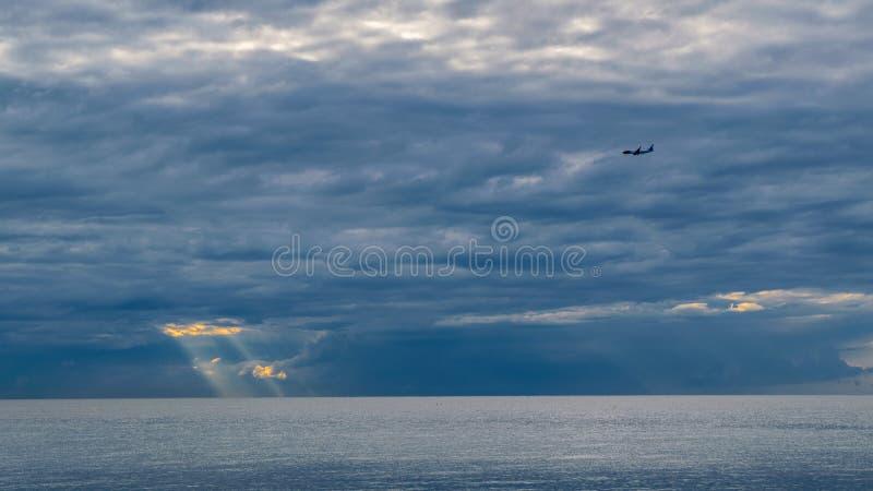 El avión vuela en el fondo de nubes sobre el mar, a través de las nubes hace su manera el sol, la riviera francesa imagenes de archivo