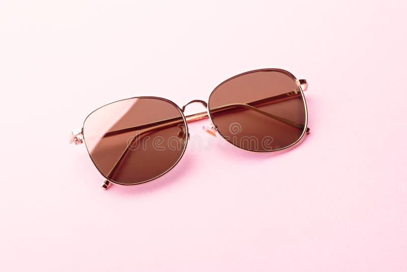 El aviador clásico duplicó las gafas de sol planas de la lente con el primer de oro del marco metálico en fondo rosado fotos de archivo