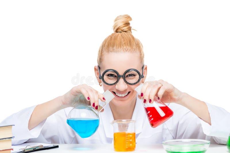 El ayudante de laboratorio feliz mezcla los líquidos en un laboratorio foto de archivo libre de regalías