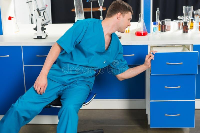 El ayudante de laboratorio masculino está buscando algo en los casos en un labo fotografía de archivo