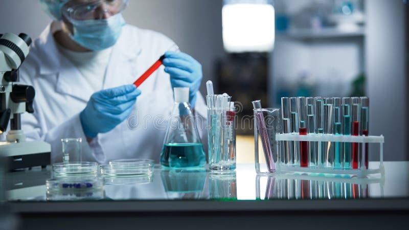 El ayudante de laboratorio que examina la muestra de sangre médica, buscando sedimenta foto de archivo libre de regalías