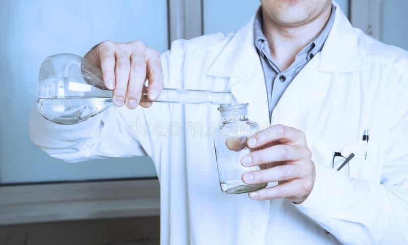 El ayudante de laboratorio vierte el líquido de un frasco fotos de archivo
