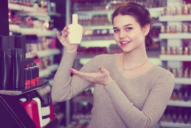 El ayudante de tienda femenino joven está demostrando el removedor polaco del nale fotos de archivo libres de regalías