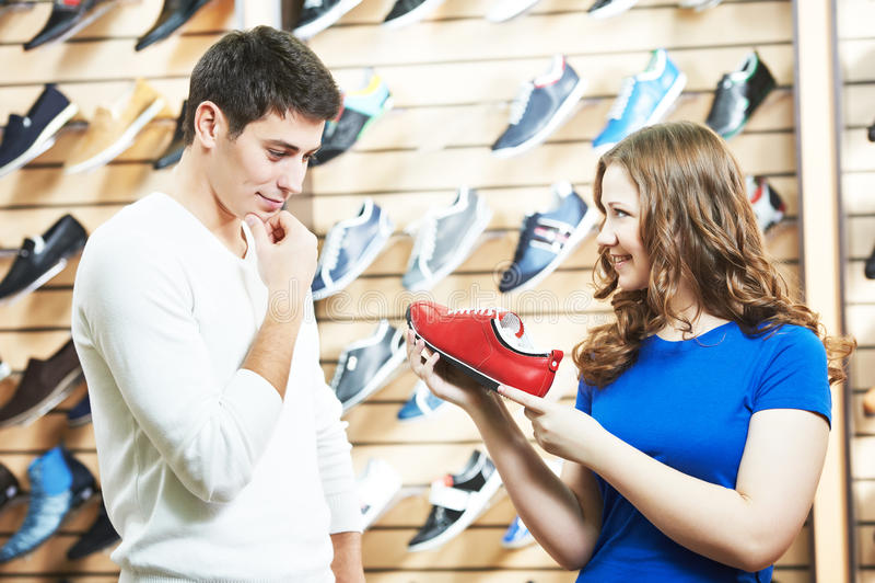 El ayudante femenino de la venta demuestra el zapato al hombre en la tienda del calzado imagenes de archivo