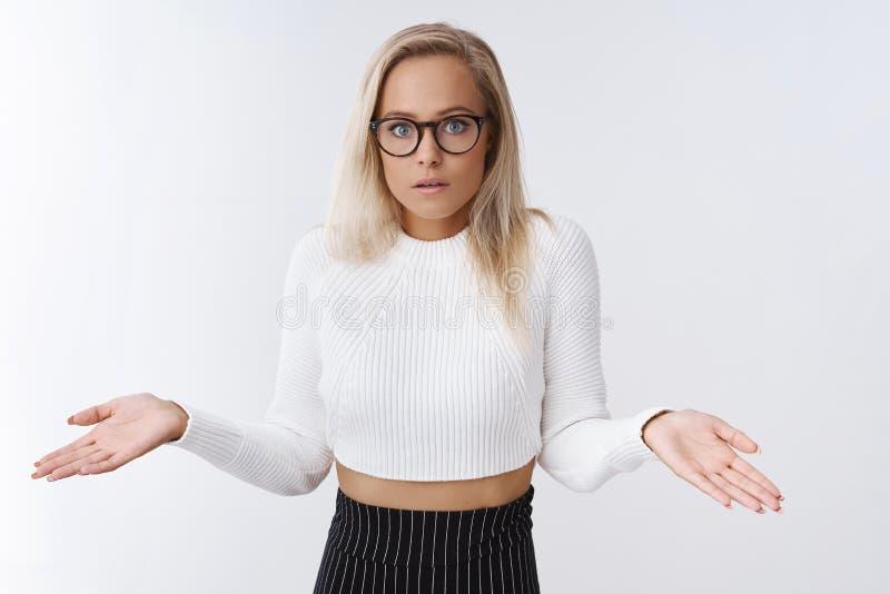 El ayudante femenino preocupante desorientado confundido en vidrios cosechó el suéter y la falda que encogía con la boca abierta  imagenes de archivo